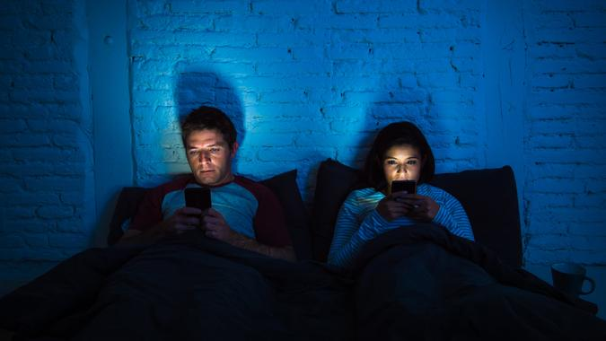 young couple at home in bed late at night using mobile phone in relationship communication problem and internet social media network concept.