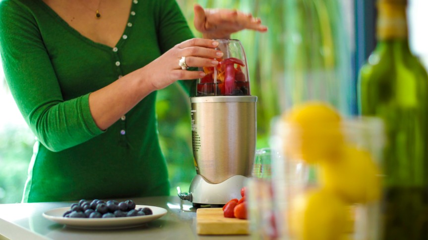 A young woman making a fruit smoothie drink using a high speed blender after loading it with fruit.
