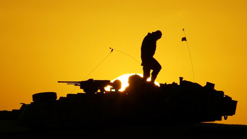 US Soldier walks atop armored tank during Iraq War