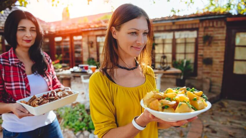 Woman carrying a bowl with roasted potatoes at backyard patio.