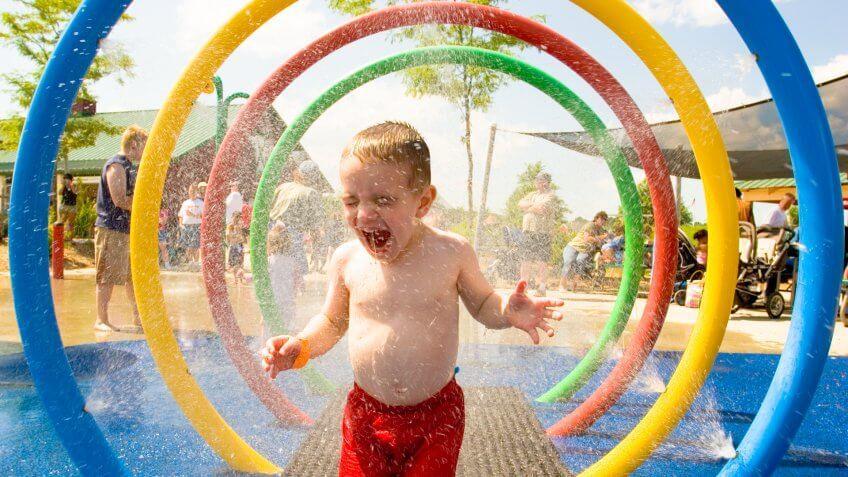 Toddler boy enjoys a spray at a splash park.