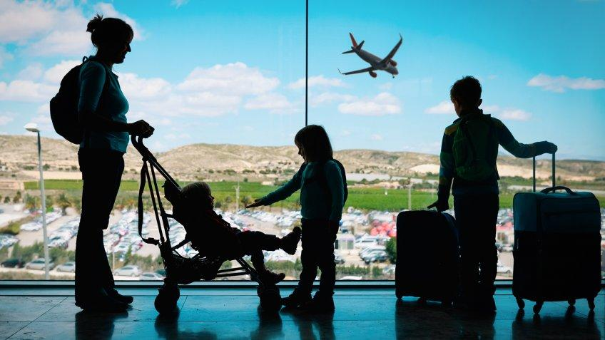 mother with kids and luggage looking at planes in airport, family travel.