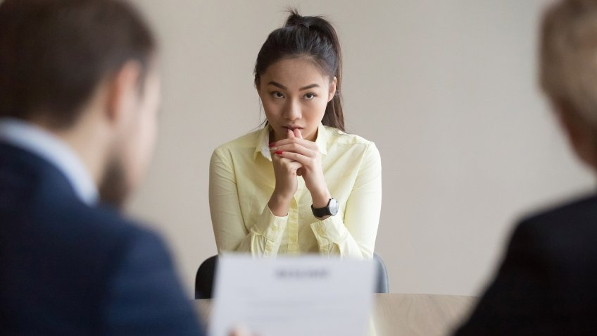 Nervous young Asian job applicant wait for recruiters question during interview in office, worried intern or trainee feel stressed applying for open position, meeting with hr managers.