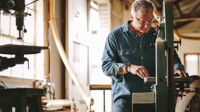 Mature male carpenter working on band saw machine in carpentry workshop.