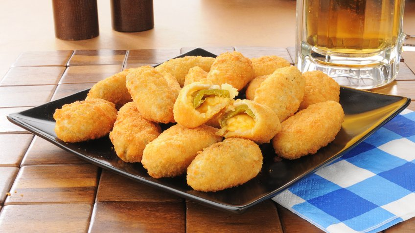 Jalapeno and cheddar cheese poppers with a mug of beer.