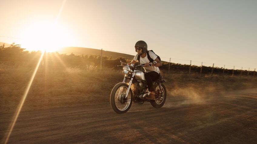 Male biker driving a vintage motorcycle on dirt road.