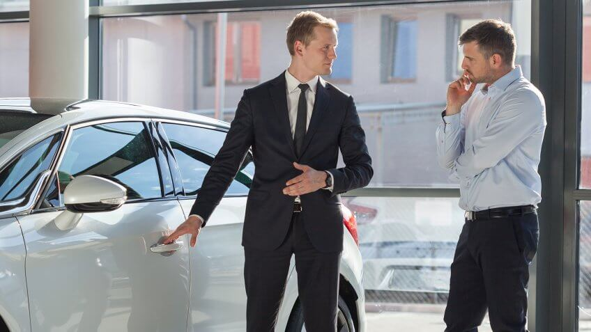 Car agent and customer in car showroom - Image.