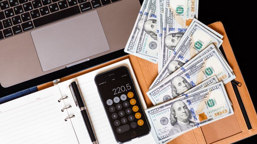 Flatlay desk: calendar, pen, cash money, phone with calculator and laptop lying on black background.
