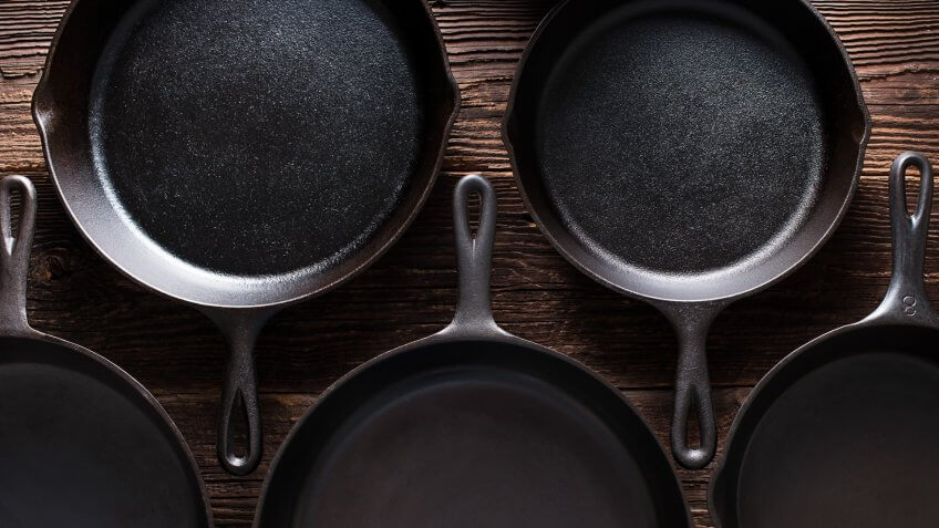 Cast Iron Skillets on Rustic Wood Table.