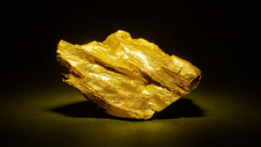Closeup of big gold nugget on a black background.