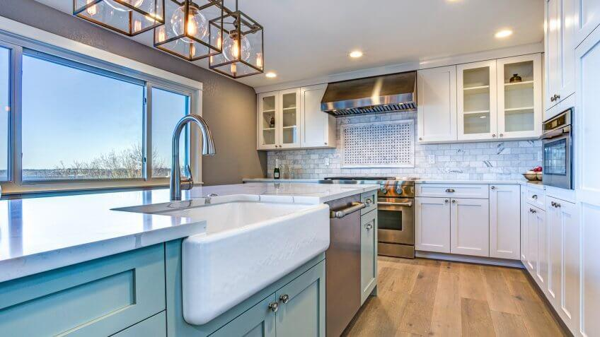 Beautiful kitchen room with green island and farmhouse sink.
