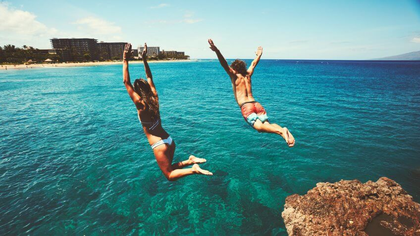 couple jumping off of cliff in ocean