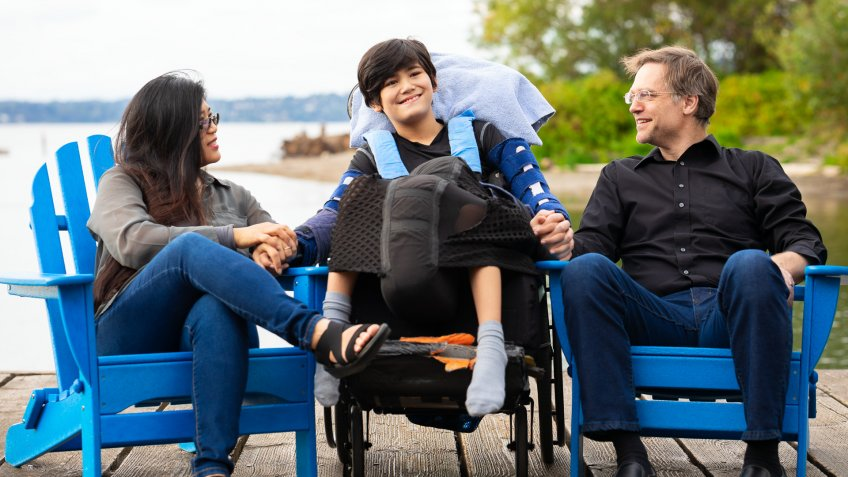 Multiracial couple sitting with disabled twelve year old son in wheelchair while sitting in blue adirondack chairs on wooden pier by lake on summer day.