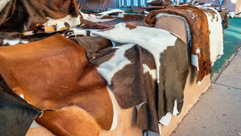 Stock photograph of colorful cowhide rugs on display in a market in downtown Santa Fe New Mexico USA.