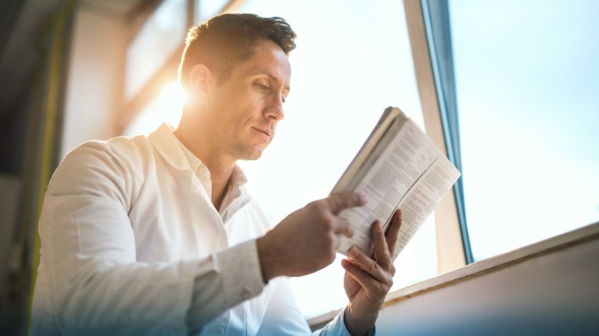 Low angle view of a mid adult doctor reading a book by the window.