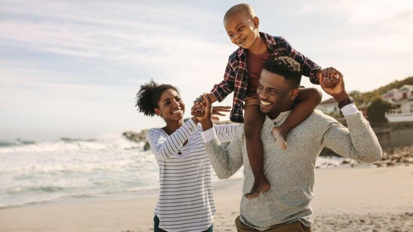Parents carrying son on shoulders on beach vacation.