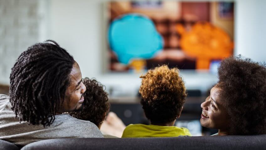 Rear view of happy African American parents communicating while watching a movie with their kids in the living room.