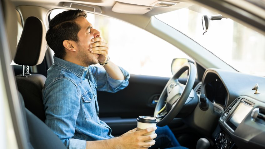 Young man feeling tired and yawning while driving a car.