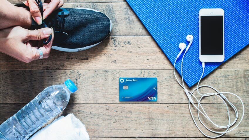 Flat lay of mobile phone with earphone and sport equipment on wood background.