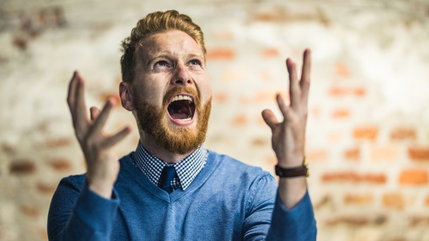 Frustrated businessman screaming of disappointment and looking up.