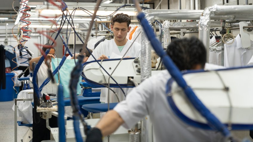 Latin american blue collar workers at an industrial laundry ironing clothes with steamers - Business industry concepts.