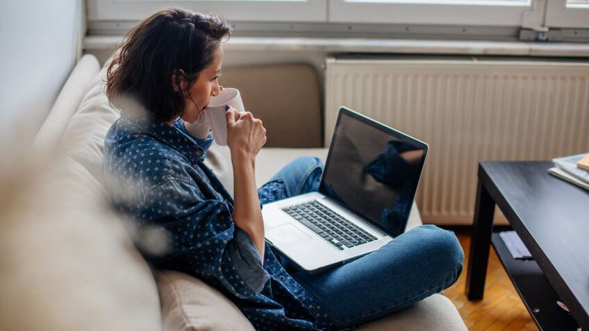 Cropped image of woman using laptop with blank screen.