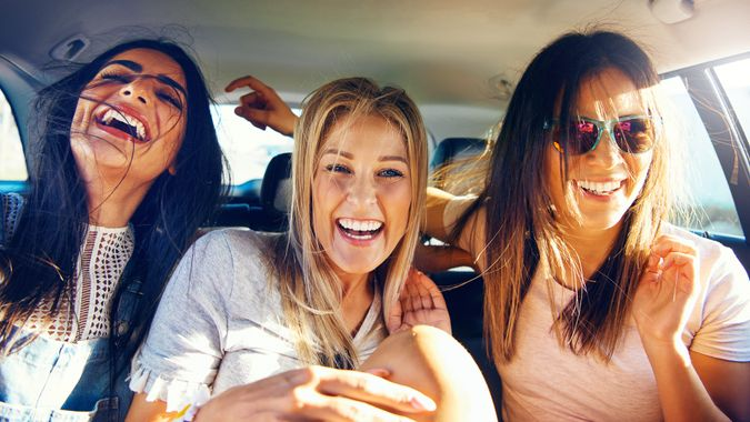 Three vivacious girlfriends on a road trip together sitting as passengers in the back of the car giggling and laughing with pleasure and enjoyment.