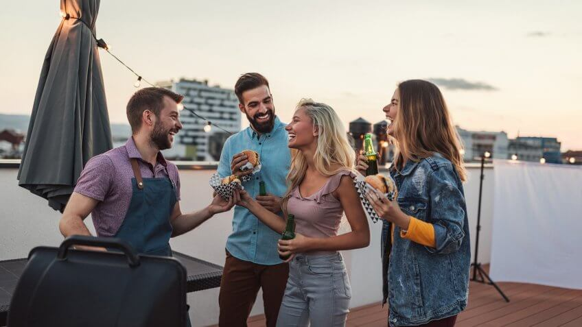 Cropped shot of four friends having fun while making barbecue on a rooftop.