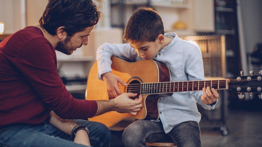 Boy teaching to play guitar in music school.