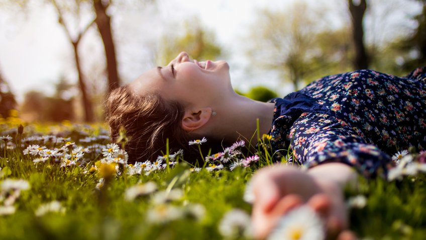 Pretty young teenage girl laying on a grass.