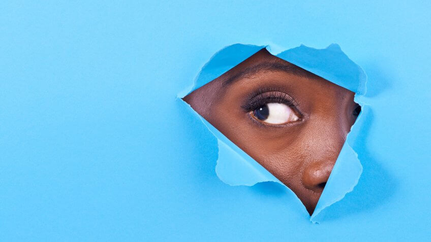 A view of a woman's eye looking through a hole in some colorful paper.