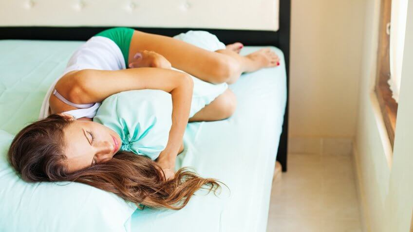 Woman in green shorts and white t-shirt lying on a bed with closed eyes (upside down photo).