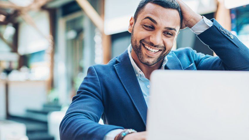 Young Middle Eastern ethnicity businessman looking at his laptop with happiness and excitement.