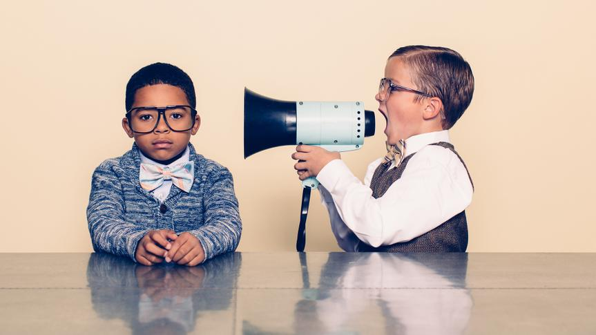 A young boy nerd shouts at the top of his voice to his co-worker through a megaphone trying to talk some sense into him but he is not listening and is ignoring him.