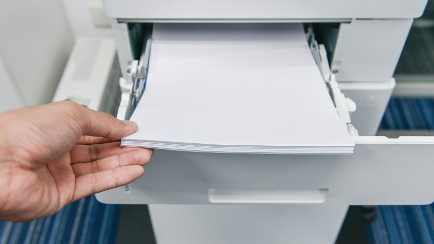 Human hand is reloading the paper to printer tray.