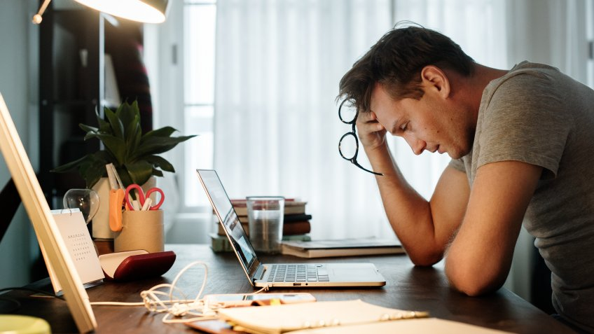 Man stressed while working on laptop.
