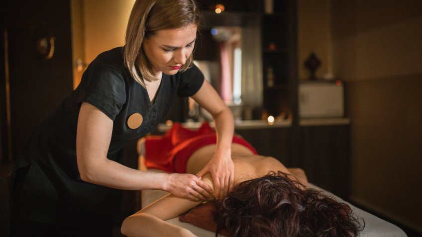Young woman relaxing and enjoying massage at spa centre.