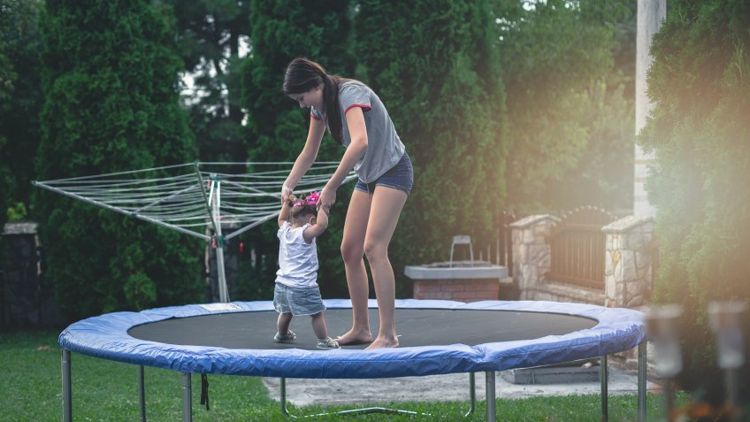 15 years old teenage girl and 17 months old baby playing on trampoline - jumping and having fun, enjoying each other.