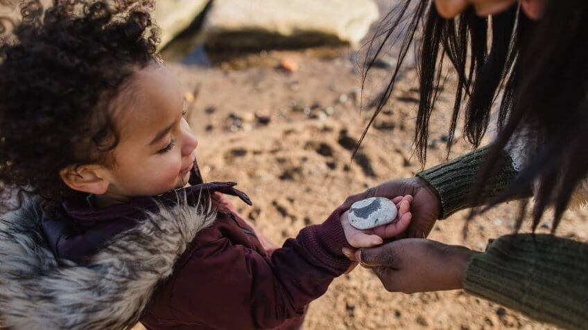 Close-up shot of a little girl handing a stone found on the beach to her mother.