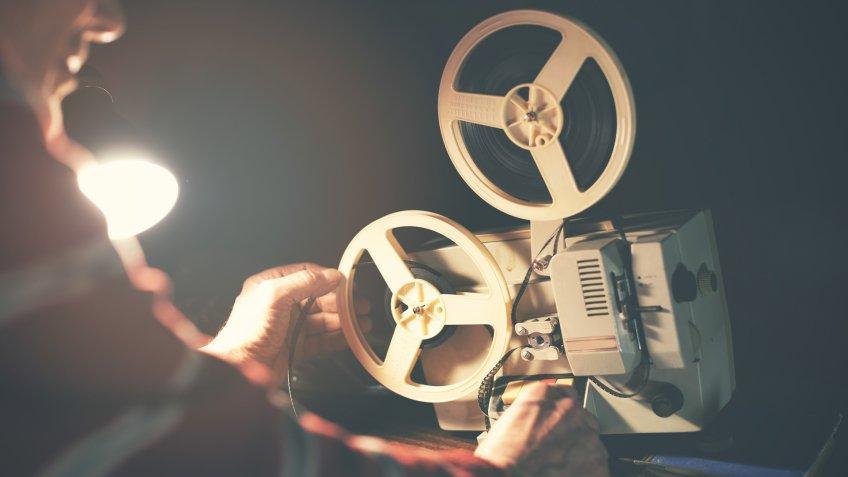 man set up film reel on vintage 8mm movie projector in dark room.