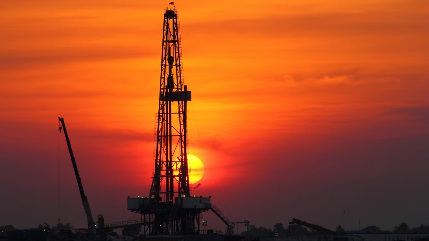 Sunset at oil drilling rig in the field.