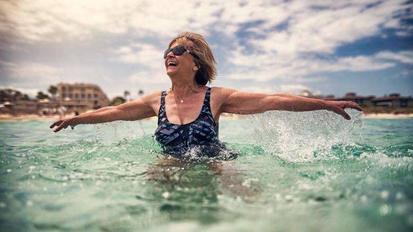 Happy senior woman enjoying summer beach vacations.