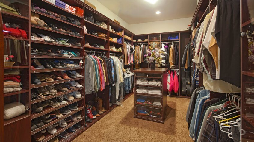 Walk in closet with organized clothing.