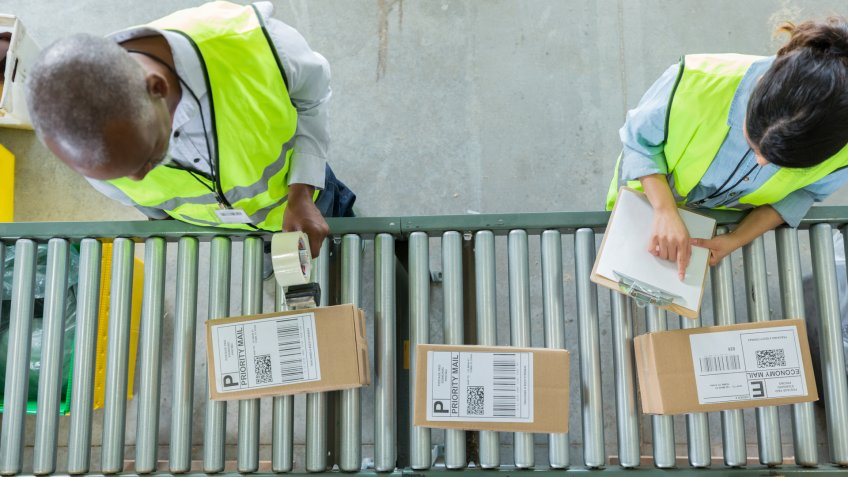 Male and female distribution warehouse employees process customers' orders.