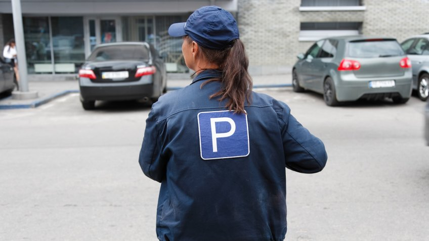 The girl in the form of a parking attendant in the city - Image.