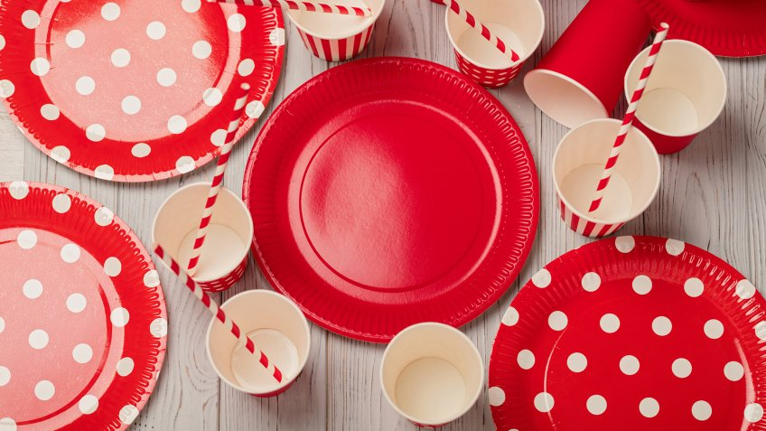 Disposable paper utensils of red and white color on a gray wooden background.
