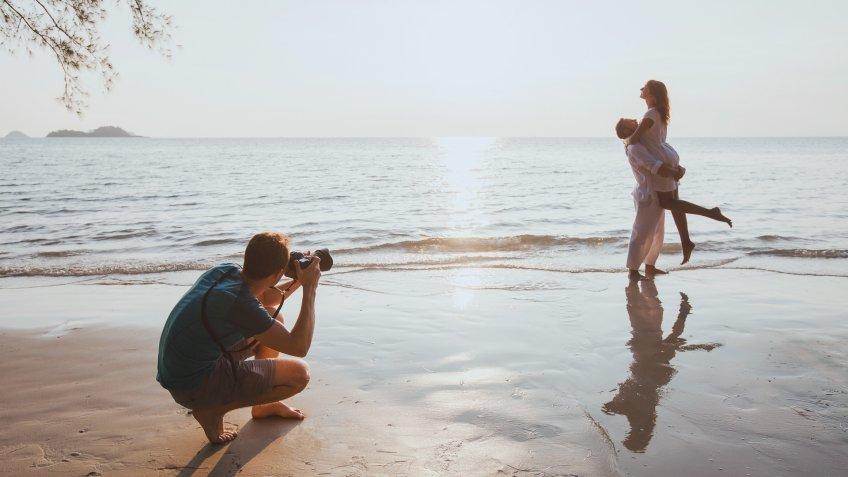 portrait photographer capturing couple on beach