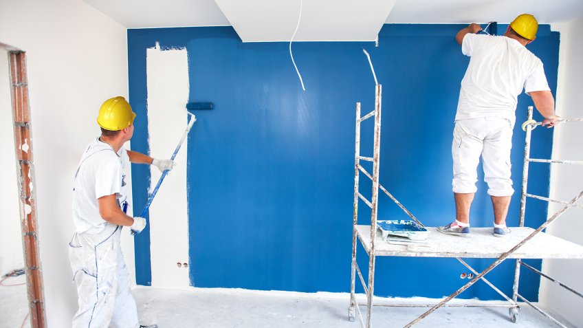 Room painter paints a wall in a new home.