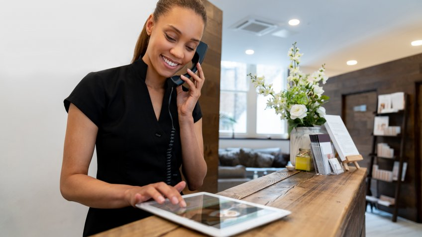 Woman working at a spa talking on the phone and making a booking - small business concepts.