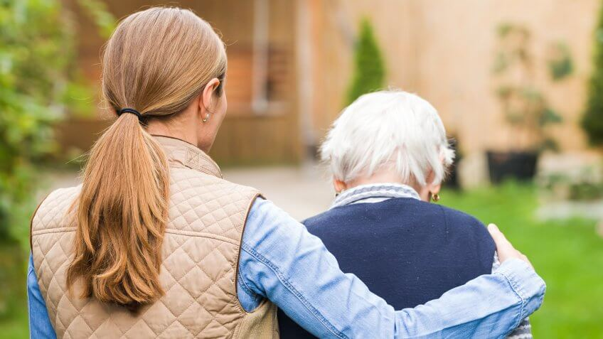 Young carer walking with the elderly woman in the park.
